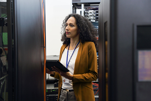 Woman in data center programing mainframe on a digital tablet.