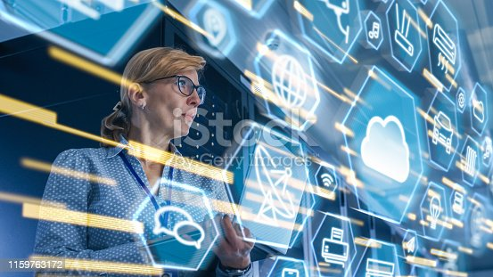 802317162 istock photo Female IT Server Specialist Standing in Data Center. View from Rack Server Cabinet with Cloud Server User Interface Icons and Visualization in the Foreground. 1159763172