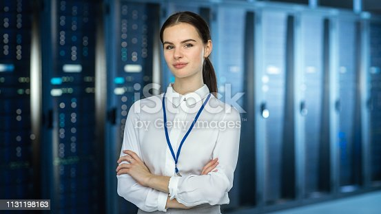 1131198396istockphoto Female IT Specialist is standing at the Camera in Data Center Next to Server Racks and Looking at the Camera. Her Arms Crossed and She Smiles to the Camera. 1131198163