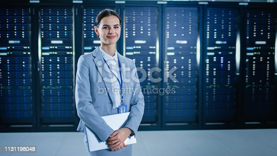 istock Female IT Specialist is Standing in Data Center Next to Server Racks, Holding Laptop and Smiling to the Camera. 1131198048