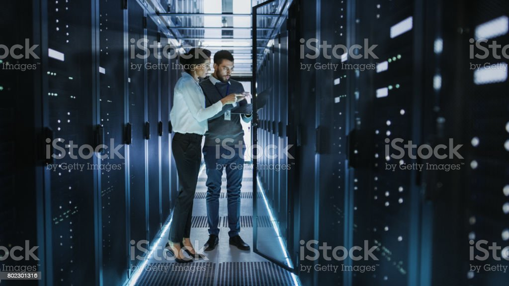 Female IT Technician and Male Server Engineer Talk and Discuss Settings of a Working Data Center. Man Holds Laptop. stock photo