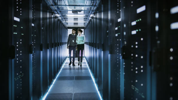 Female IT Technician and Male Server Engineer Talk and Discuss. They are in Working Data Center full of Rack Servers. Woman Holds Laptop. stock photo