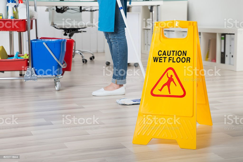 Female Janitor Mopping Wooden Floor With Caution Sign stock photo