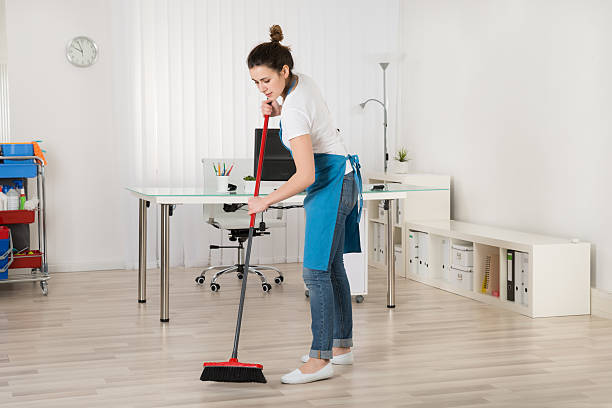 Female Janitor Sweeping Floor With Broom stock photo