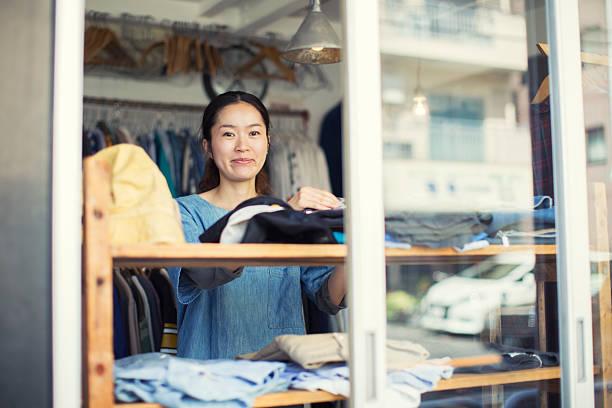 female japanese resale shop owner in her store - einzelhandelsarbeiter stock-fotos und bilder