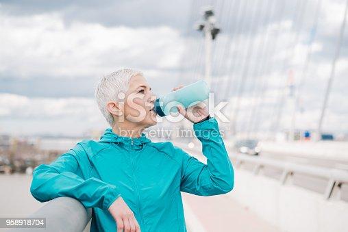 1057638814 istock photo Female jogger drinking water 958918704