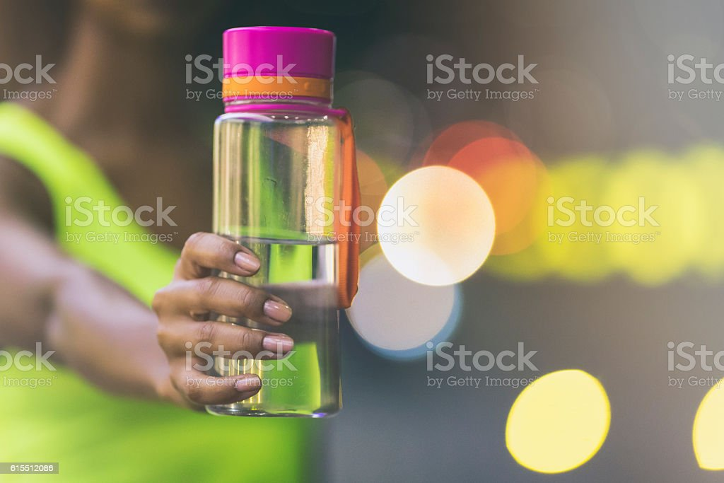 Female jogger holding a bottle of water stock photo