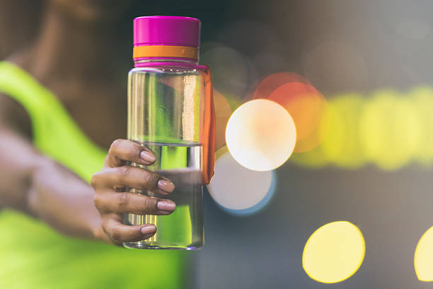 Female jogger holding a bottle of water - foto de stock
