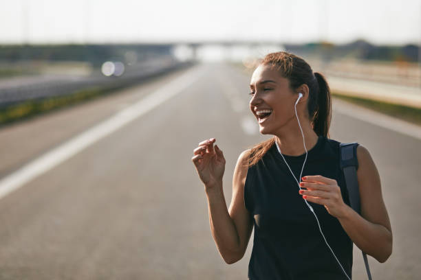 Female jogger listening to music while preparing for run