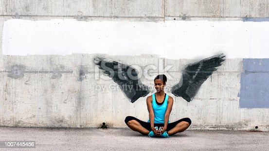 Young woman sitting on the floor, stretching in front of a concrete wall with wings graffiti. The graffiti is not real, the image of wings is my own.