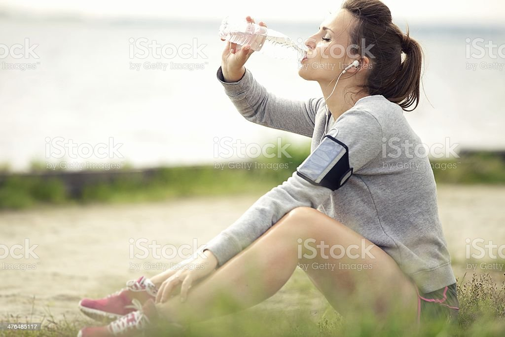 Female Jogger Resting and Drinking Bottled Water royalty-free stock photo