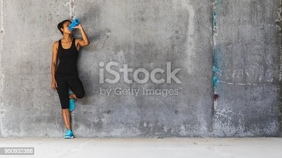 Young woman leaning on the concrete wall, resting and drinking water