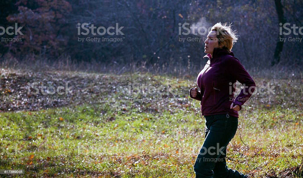 Female jogger running at cold morning rising breath vapour stock photo