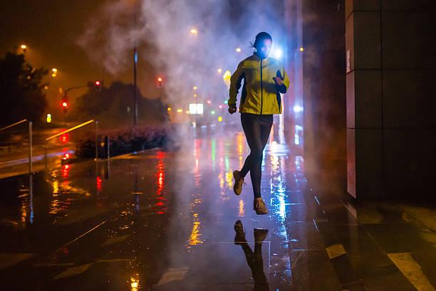 Impulsor mujer corriendo en la lluvia en la ciudad de noche - foto de stock