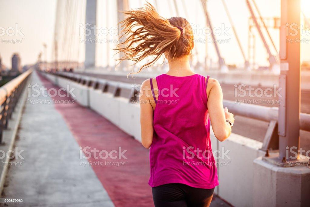 Female jogger running on the bridge stock photo
