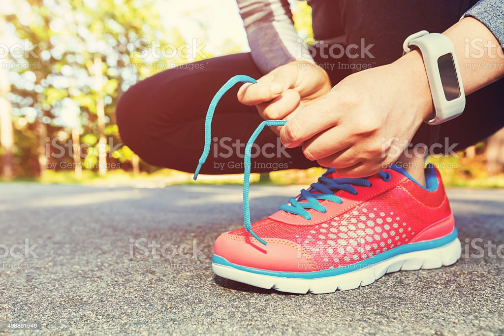 Female jogger tying her running shoes for a jog stock photo