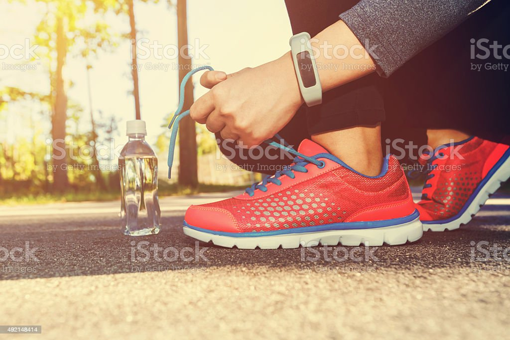 Female jogger tying her running shoes stock photo