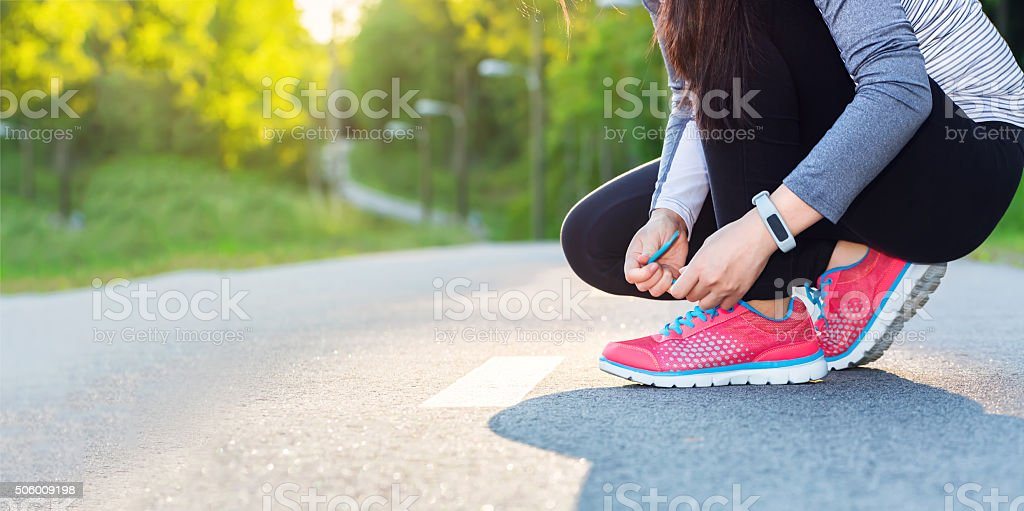 Female jogger tying her shoes stock photo