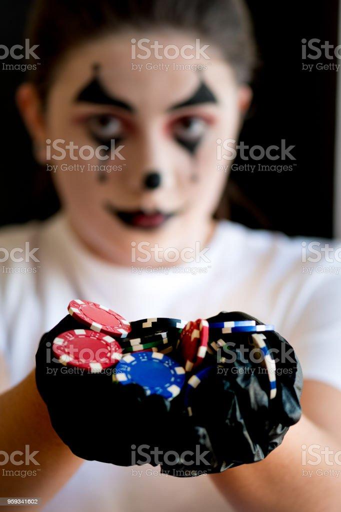 female joker showing a handful of casino chips stock photo