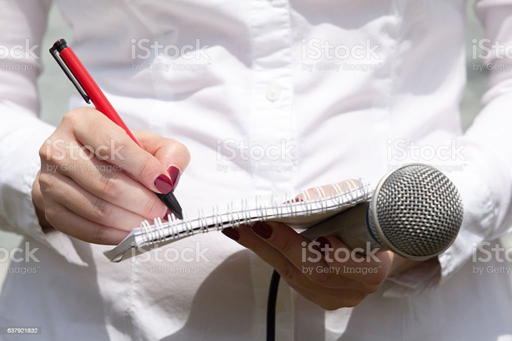 Female journalist at news conference, writing notes, holding microphone stock photo