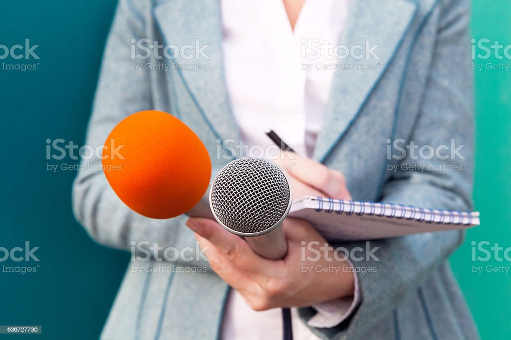 Female journalist at news conference, writing notes, holding microphones stock photo