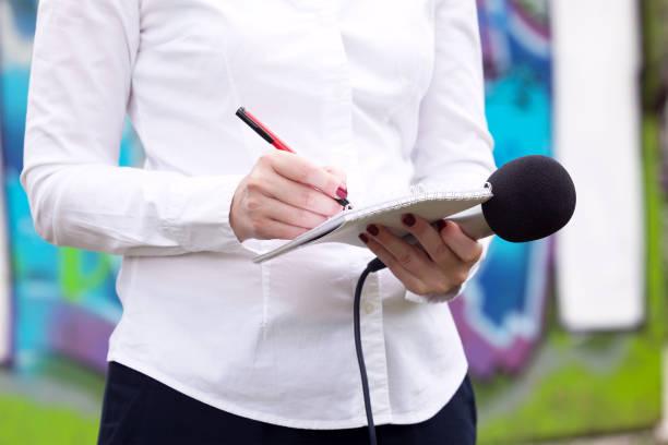 Journalistin bei Pressekonferenz, Schreiben von Notizen, mit Mikrofon – Foto