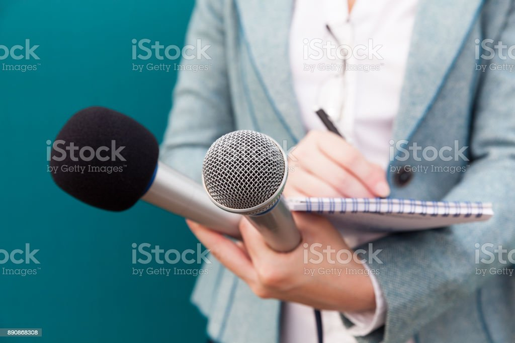 Female journalist at press conference, writing notes, holding microphone stock photo
