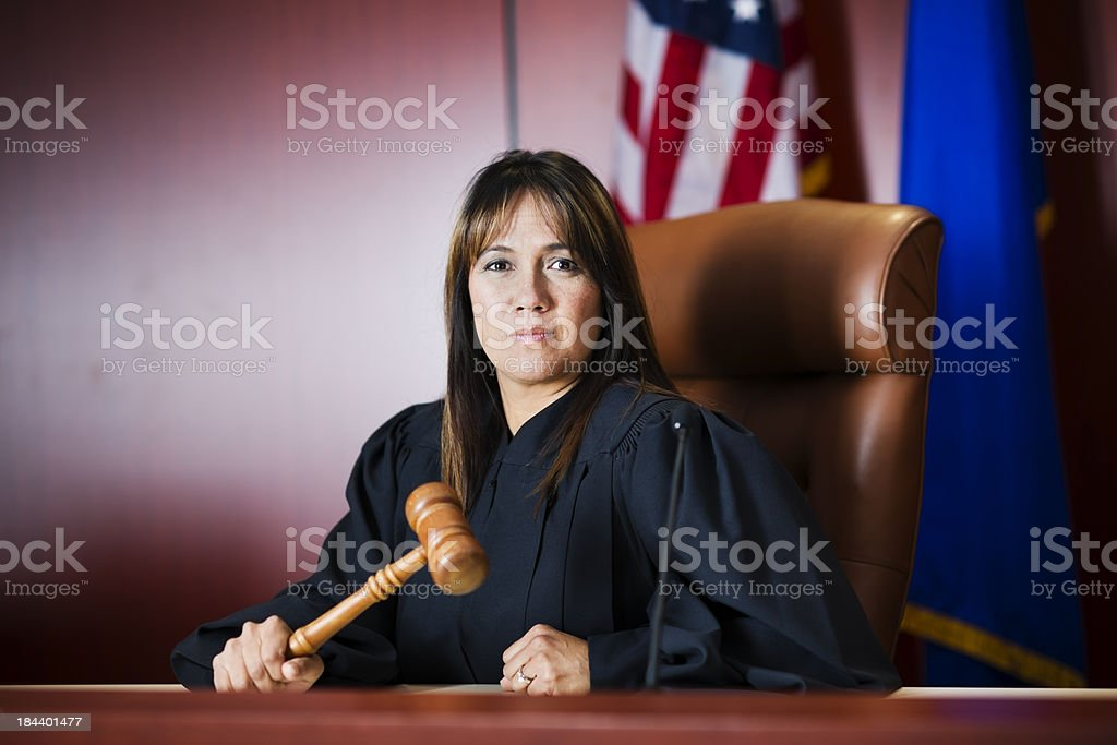Female judge sitting in court holding her gavel stock photo