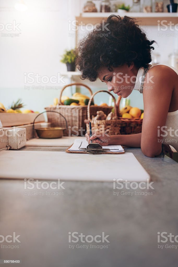 Female juice bar owner calculating expenses stock photo