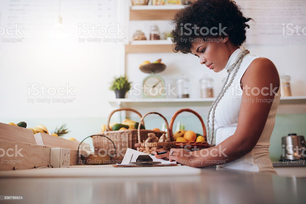 Female juice bar owner doing account stock photo