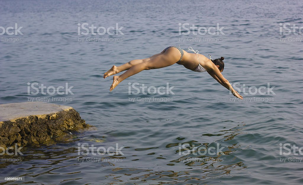 Female jumping into the water stock photo