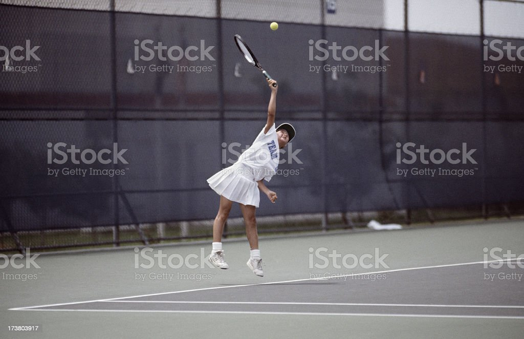 female Junior tennis player serving ball royalty-free stock photo