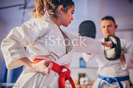 Young female karate player with trainer using focus mitts during training