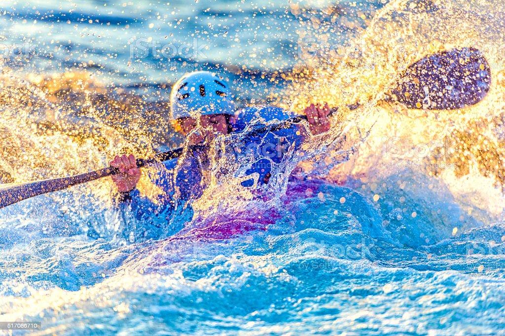 Female kayaker paddling in whitewater stock photo