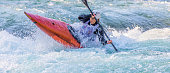 Kayaker paddling hard through heavy whitewater.