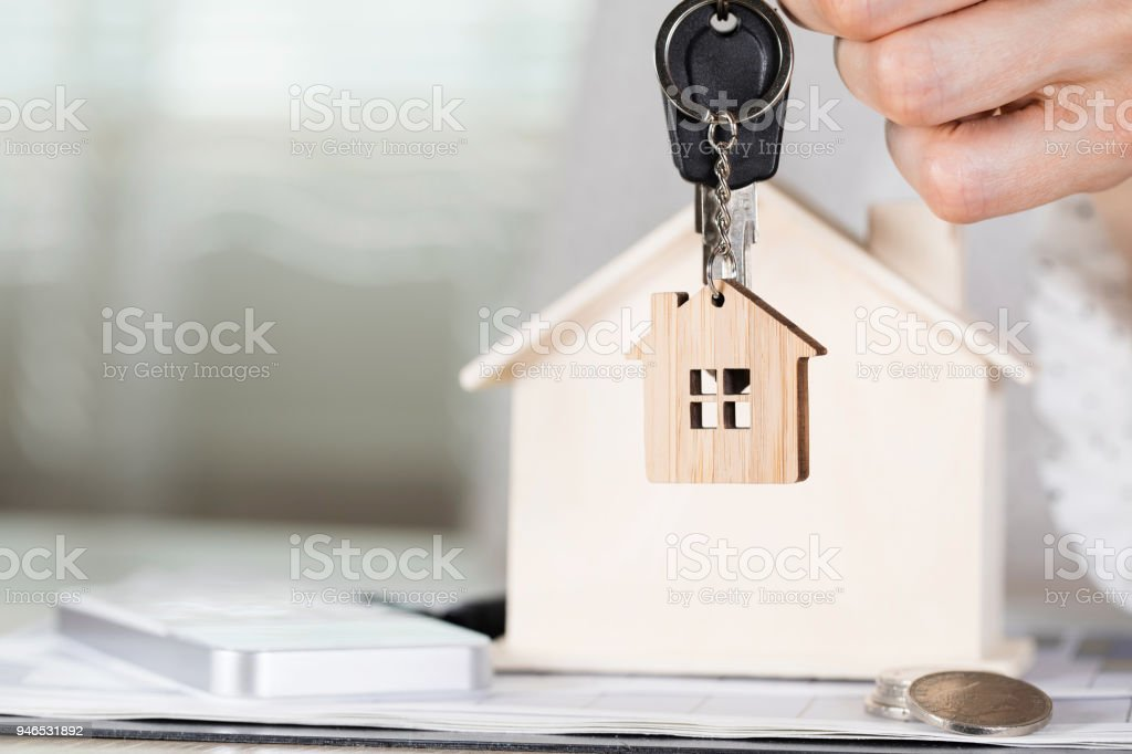 Female keeps house key on a key hanger in front of a wooden house. stock photo