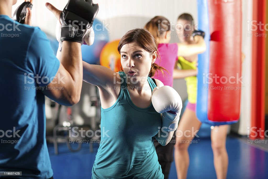 Female kick boxer with trainer in sparring stock photo