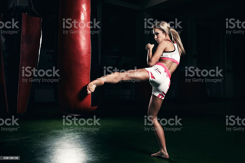 Female kickboxer fighter training with a punching bag stock photo