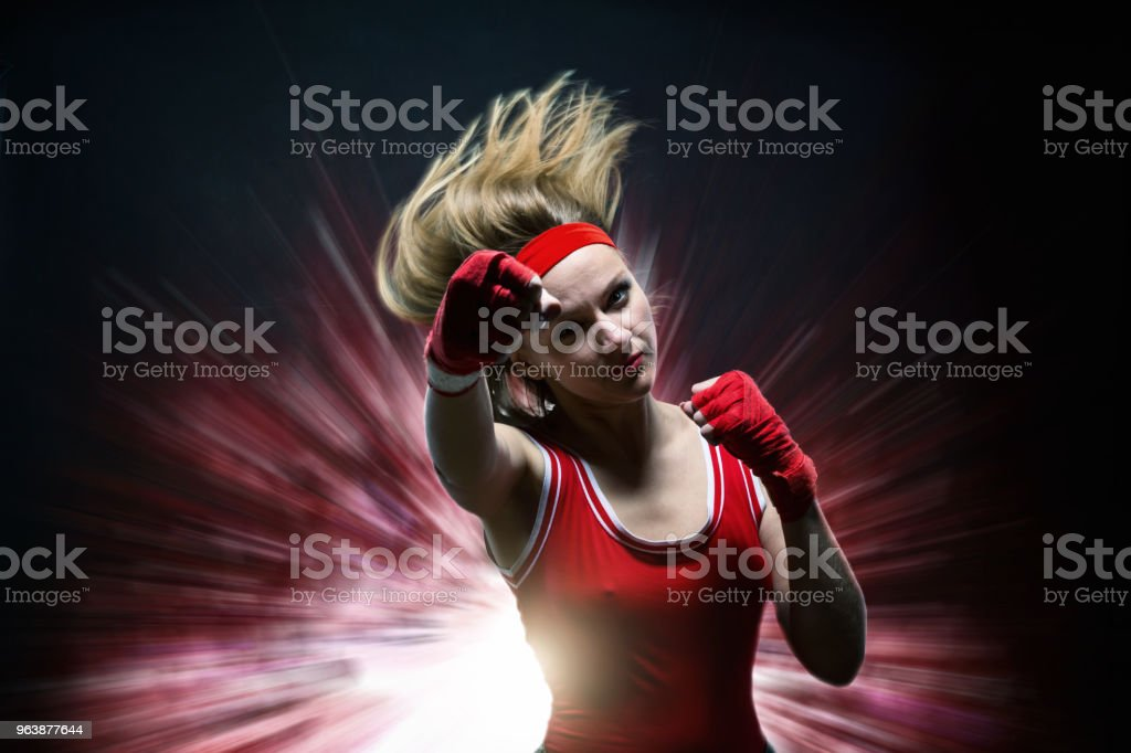 Female kickboxer in boxing bandages makes punch - Royalty-free Adult Stock Photo