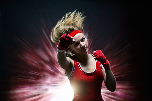 Female Kickboxer In Boxing Bandages Makes Punch Stock Photo - Download Image Now