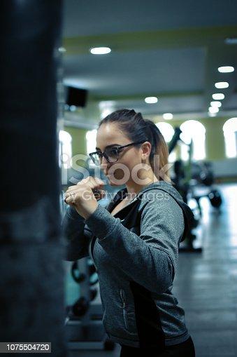 873932790 istock photo Female kickboxer training with a punching bag 1075504720