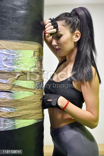 873932790 istock photo Female kickboxer training with a punching bag 1131109741