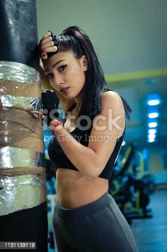 873932790 istock photo Female kickboxer training with a punching bag 1131139119