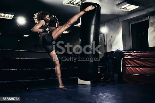 Photo of a fit female kickboxer training with a punching bag in a boxing hall. She is jumping on a boxing ring in an underground fight club, training kicking.
