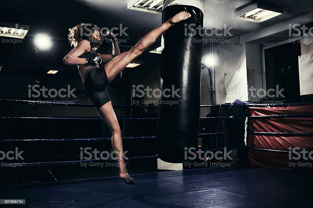 Female kickboxer training with a punching bag stock photo
