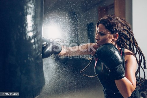istock Female kickboxer training with a punching bag 873719468