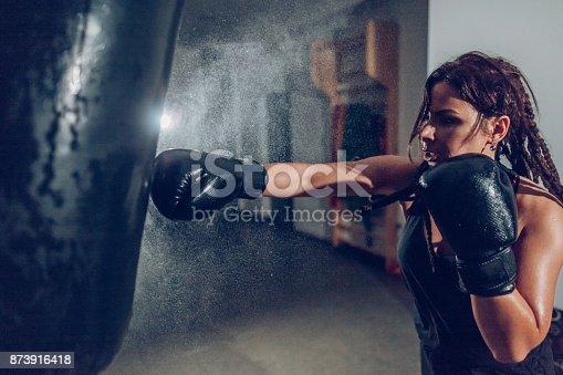 873932790 istock photo Female kickboxer training with a punching bag 873916418