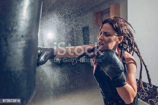873932790 istock photo Female kickboxer training with a punching bag 873923816