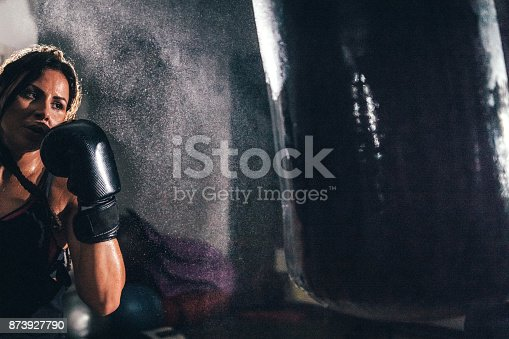 873932790 istock photo Female kickboxer training with a punching bag 873927790