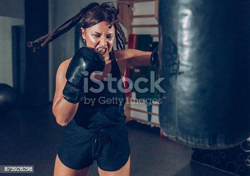 873932790 istock photo Female kickboxer training with a punching bag 873928298